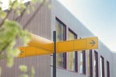 Gelbes Verkehrsschild oder leere Verkehrsschilder, die Richtung gegen ein Gebäude zeigen lizenzfreie stockfotos