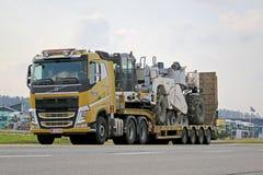 Gelbes Volvo FH schleppt Schwermaschinen Stockbilder
