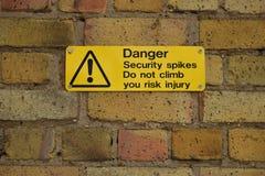 Gelbes Warnschild auf einer Backsteinmauer Stockbild
