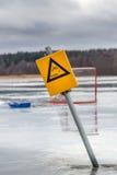 Gelbes Warnzeichen- und Hockeyziel auf dem nassen Schmelzen gefrieren auf gefrorenem See, Schweden Lizenzfreies Stockfoto