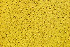 Gelbes wasserdichtes Material, Rissendstoff mit Wassertropfen lizenzfreie stockbilder