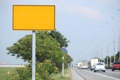 Gelbes Zeichen auf der Straße Stockbild