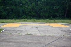 Gelbes Zeichen auf konkretem Hubschrauber-Landeplatz Lizenzfreies Stockbild
