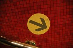 Gelbes Zeichen auf rotem Hintergrund in Hong Kong-U-Bahn Lizenzfreie Stockbilder