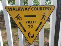 Gelbes Zeichen auf weißem Zaun auf Gehweghöflichkeit und -c$erbringen stockfotos