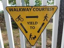 Gelbes Zeichen auf weißem Zaun auf Gehweghöflichkeit und -c$erbringen lizenzfreies stockbild
