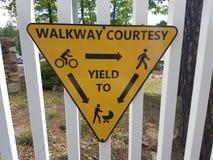 Gelbes Zeichen auf weißem Zaun auf Gehweghöflichkeit und -c$erbringen stockfoto