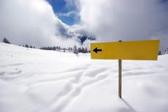 Gelbes Zeichen mit Pfeil in den Bergen Stockfoto
