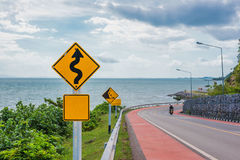 Gelbes Zeichen mit Symbol der kurvenreichen Straße im Landschaftssee- und -himmelhintergrund Stockfotos