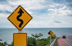 Gelbes Zeichen mit Symbol der kurvenreichen Straße im Landschaftssee- und -himmelhintergrund Lizenzfreies Stockbild