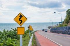 Gelbes Zeichen mit Symbol der kurvenreichen Straße im Landschaftssee- und -himmelhintergrund Stockbilder