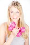 Gelächelte Frau, die zwei Gewichte anhält Stockbilder