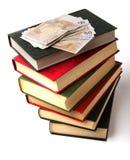 Geld über Buchstapel Stockfoto
