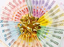Geld als Geschenk. goldenes Farbband auf Eurobanknoten Stockfotografie