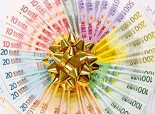 Geld als gift. gouden lint op euro bankbiljetten Stock Fotografie