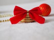 Geld als Weihnachtsgeschenk, Münzen auf einem Schnee mit rotem Bogen lizenzfreie stockfotografie