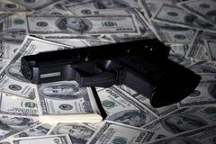 Geld & Pistool. Misdadige zaken. stock foto