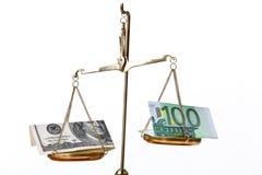 Geld auf balancierenden Skalen Stockbilder