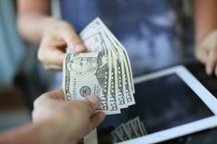 Geld auf dem Hintergrund der Tablette Stockfotografie