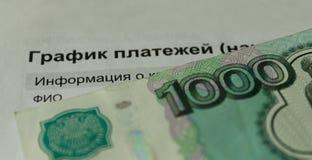 Geld auf dem Hintergrund des Zeitplanes Stockfotografie