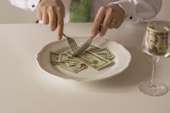 Geld auf einer Platte, die wie Lebensmittel mit einem Messer und einer Gabel geschnitten wird Stockfotos