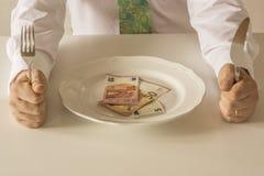 Geld auf einer Platte, die wie Lebensmittel mit einem Messer und einer Gabel geschnitten wird Lizenzfreie Stockfotos