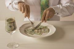 Geld auf einer Platte, die wie Lebensmittel mit einem Messer und einer Gabel geschnitten wird Stockfoto