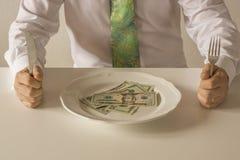 Geld auf einer Platte, die wie Lebensmittel mit einem Messer und einer Gabel geschnitten wird Lizenzfreie Stockbilder