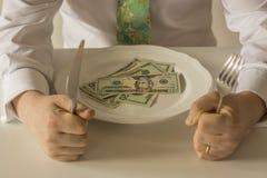 Geld auf einer Platte, die wie Lebensmittel mit einem Messer und einer Gabel geschnitten wird Lizenzfreie Stockfotografie