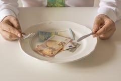 Geld auf einer Platte, die wie Lebensmittel mit einem Messer und einer Gabel geschnitten wird Lizenzfreies Stockbild