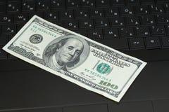 Geld auf einer Tastatur Lizenzfreies Stockbild