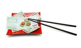 Geld auf Platte mit den Ess-Stäbchen getrennt stockbild