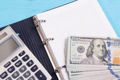 Geld, calculator en lege blocnote Stock Afbeelding