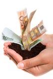 Geld, das in den Händen wächst Stockbild