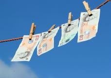 Geld, das an einer waschenden Linie, vielleicht Geldwäsche hängt. Lizenzfreies Stockfoto