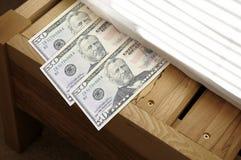 Geld dat onder matras wordt weggemoffeld Stock Afbeeldingen