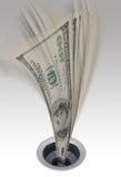 Geld dat onderaan het afvoerkanaal gaat Stock Foto's