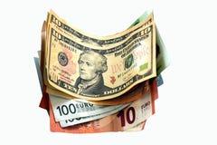 Geld - de dollars, de euro en andere munten liggen op de witte oppervlakte van de lijst stock afbeelding