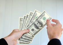 Geld in de handen stock foto's
