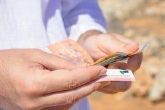 Geld in de handen van een mens onder de hete zon van de woestijn Royalty-vrije Stock Foto's