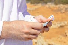 Geld in de handen van een mens onder de hete zon van de woestijn Stock Foto
