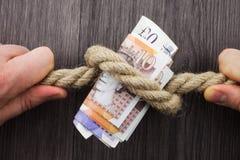 Geld in de knoop met handen op de einden wordt geknoopt dat Economieconcept met geld in het beeld royalty-vrije stock foto