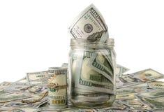 Geld in de kruik die op Amerikaanse dollarbankbiljetten plaatsen Royalty-vrije Stock Foto's