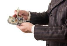 Geld in den Geschäftsmannhänden lokalisiert auf Weiß Lizenzfreie Stockfotos