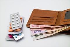 Geld in der braunen Geldbörse mit den Blasen von Pillen Lizenzfreie Stockfotografie