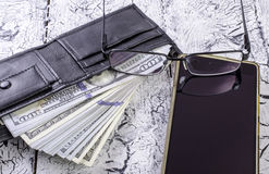 Geld in der Geldbörse, in den Gläsern und in einem Smartphone Lizenzfreie Stockfotografie