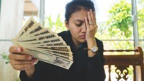 Geld in der Hand mit Aussagenpapier und dem Fühlen stressig im finnancial Konzept Stockfotos