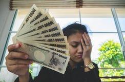 Geld in der Hand mit Aussagenpapier und dem Fühlen stressig im finnancial Konzept Stockfoto