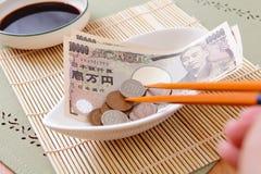 Geld der japanischen Yen in der Schüssel mit Ess-Stäbchen Stockfoto