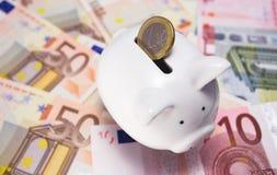 Geld in der piggy Querneigung lizenzfreie stockbilder